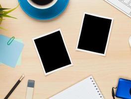 fotoramar på kontorsbordet med anteckningsblock, dator och kamera foto