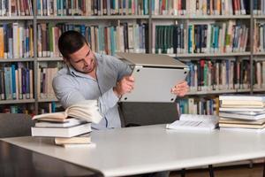 rasande student som kastar sin bärbara dator foto