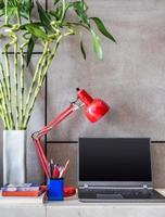 bärbar dator, lampa med vas av lycklig bambu i moderna rum