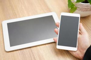 TabletPC och mobiltelefon i handen foto