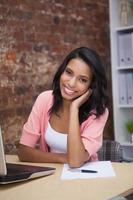 glad kvinna med sin bärbara dator som ler mot kameran foto