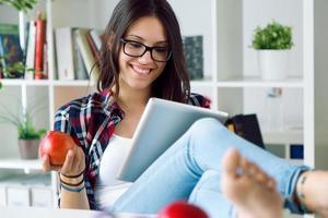 vacker ung kvinna som använder sin digitala tablett hemma. foto