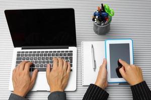 ovanifrån av man och kvinna som använder bärbar dator och surfplatta foto