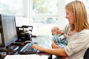 en mamma som håller sitt barn och arbetar hemifrån foto