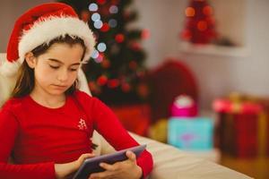 festlig liten flicka som använder TabletPC på soffan foto
