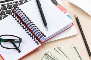 kontorsbord med pc, leveranser och pengar