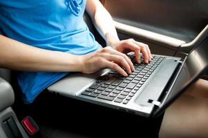oigenkännlig kvinna som sitter i bilen med laptop på knäna foto