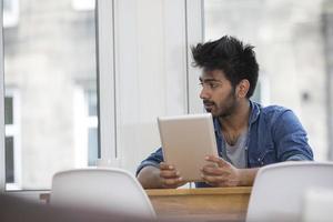 asiatisk man sitter vid ett bord och läser en surfplatta. foto