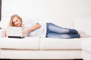 kvinna i soffan med laptop foto