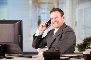 affärsman i telefon på sitt kontor foto