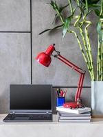 modernt skrivbord med laptop, lampa och vas med blommor