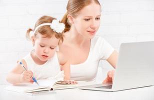 familj mor och barn baby hemma arbetar på datorn foto