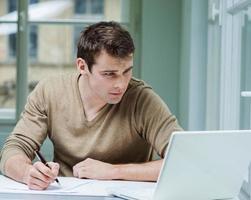 ung affärsman tittar på bärbar dator medan han skriver på dokument foto