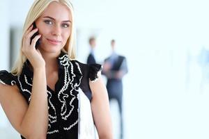 vacker affärskvinna med mobiltelefon, står på kontoret