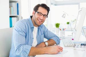 fotoredaktör som skriver på ett papper medan du tittar på kameran foto
