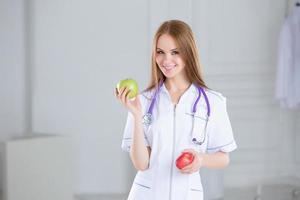 läkare som håller ett grönt äpple. begreppet hälsosam mat.