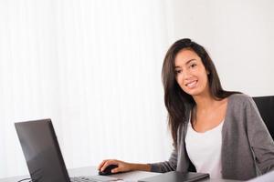 glad ung kvinna kontorsskrivbord och arbetar med bärbar dator foto