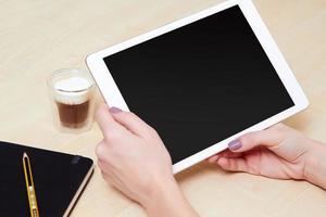 flicka tittar på en digital surfplatta, med ett kaffe foto