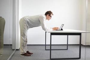 övning under kontorsarbete - man med surfplattan på sitt kontor foto