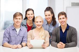 leende studenter med surfplatta i skolan foto