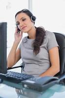 avslappnad attraktiv sekreterare som bär headset