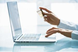kvinna shoppar med laptop och kreditkort .indoor.close-up foto