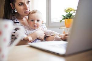en ung mamma och hennes baby som arbetar hemifrån foto