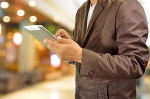ung man händer som håller tabletten i köpcentret foto