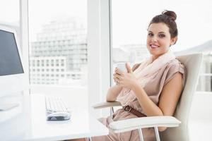 avslappnad affärskvinna som håller varm dryck foto