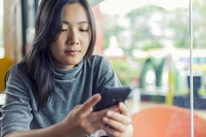 kvinnor använder smartphone för affärer på café foto