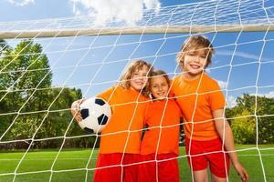 tre positiva flickor i uniformer med fotboll foto