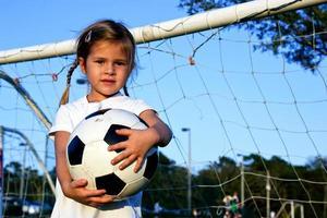 liten flicka som håller en fotboll foto