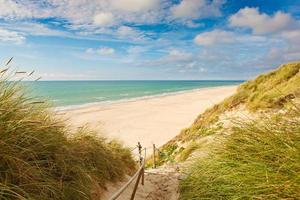 havet med sanddyner och färgglad himmel foto