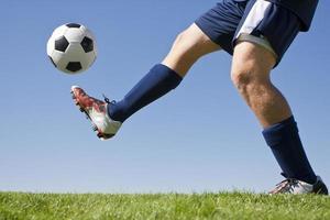 fotbollsspelare och grönt gräs som sparkar upp en fotboll foto
