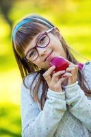 liten flickastående som äter rött äpple i trädgården foto