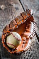 gammal baseballboll och handske foto