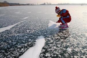 liten flicka spelar på isen av sjön. foto