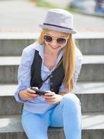 hipster tjej skriver sms när man sitter på trappan foto