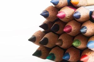 färgglada träpennor på vit bakgrund foto