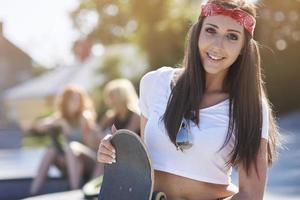 tonårsflicka med sitt skateboard foto