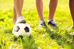 fötter och fotboll foto