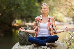 ung vandrare yoga meditation i bergsdalen foto