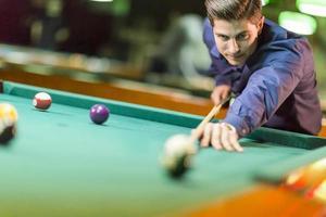 ung man spelar pool foto