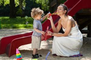 mamma och pojke gör bubblor foto