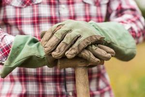 bonde som bär checkskjorta lutad på en spade foto