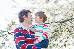 ung far och liten pojke i blommande trädgård foto