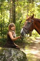 vacker flicka och brun häst porträtt i mystisk skog foto