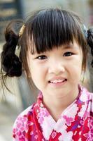 lilla asiatiska barn i japansk traditionell dräkt foto