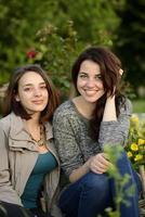 två vackra unga kvinnor som ler bredvid en blommabakgrund foto
