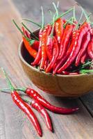 röda chilipeppar i träskål på träbord foto